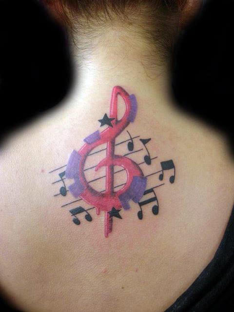 Татуировка на спине у девушки скрипичный ключ и ноты