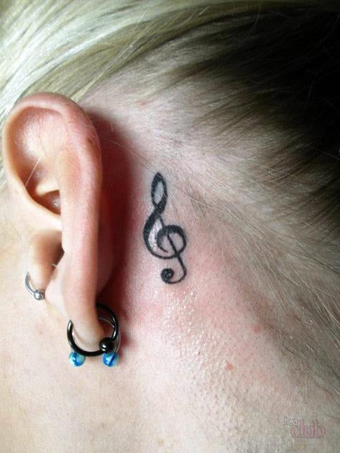 Тату скрипичный ключ за ухом у девушки