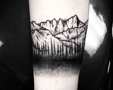 Татуировка в стиле дотворк со скалами на руке