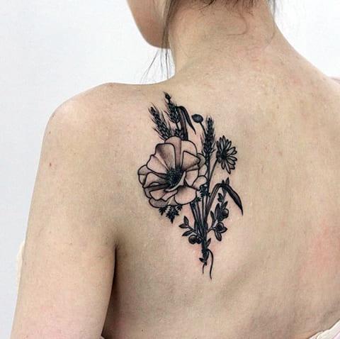 Тату цветы ромашка на лопатке у девушки