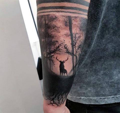 Олень в лесу - татуировка на руке
