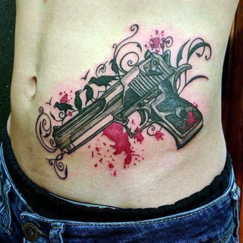 Тату с пистолетом в стиле акварель на животе у мужчины