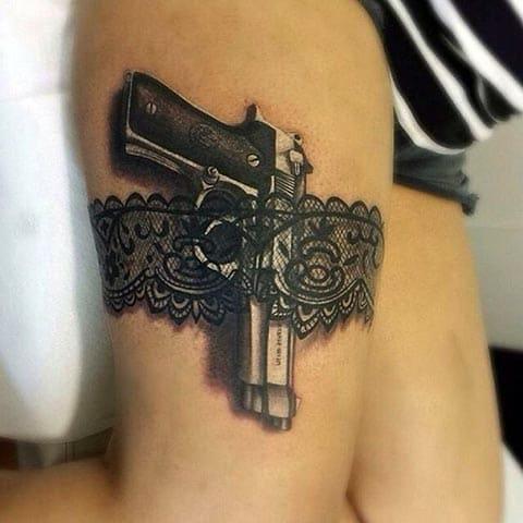 Тату пистолет в подвязке на бедре у девушки - фото