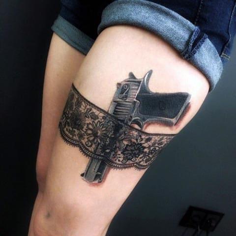 Татуировка на бедре девушки с пистолетом в подвязке