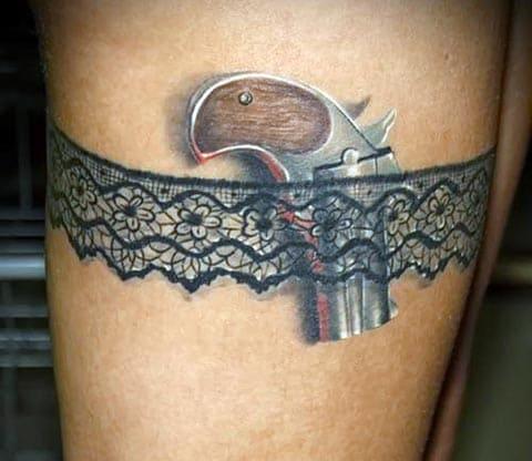 Тату с маленьким пистолетом на ноге у девушки