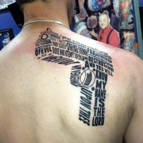 Тату из надписей в форме пистолета на лопатке