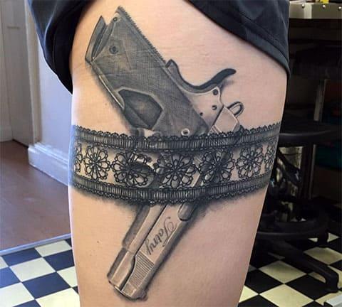 Тату пистолет на бедре в подвязке у девушки