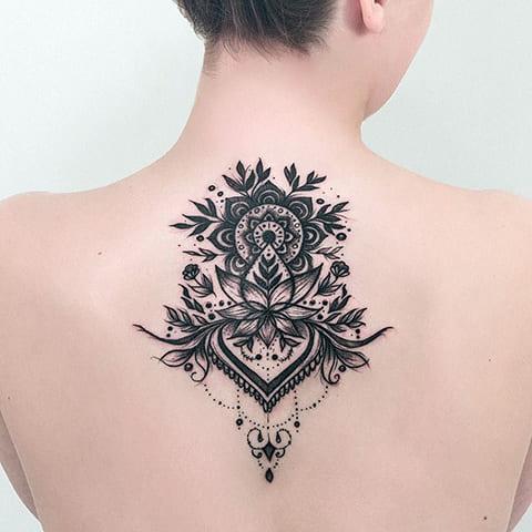 Татуировка мандала у девушки на спине