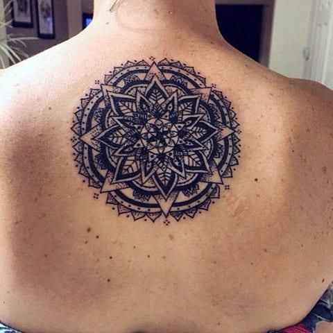 Татуировка мандала у девушки на спине - фото