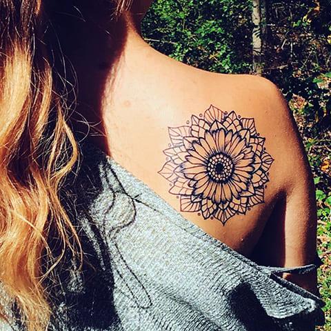 Татуировка мандала у девушки на лопатке