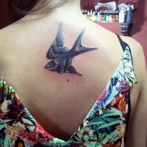 Татуировка ласточка на спине у девушки
