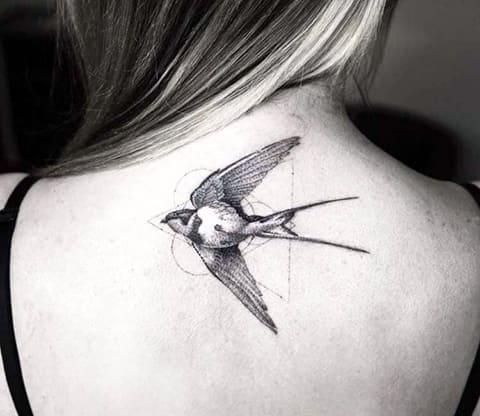 Тату ласточка в стиле геометрия на спине у девушки - фото