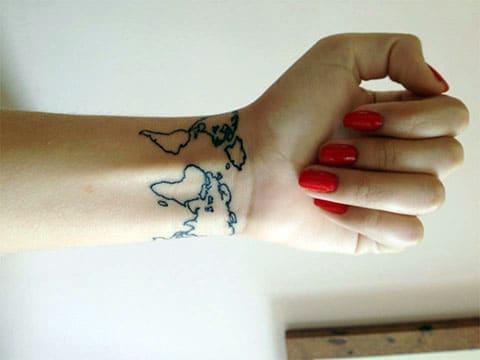 Татуировка карта мира на запястье у девушки