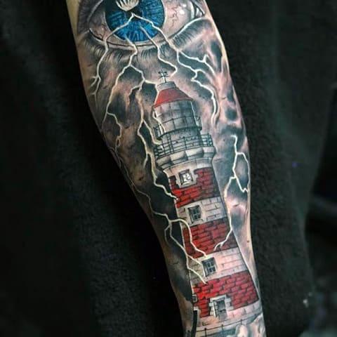 Тату маяк с глазом и молниями на руке - фото