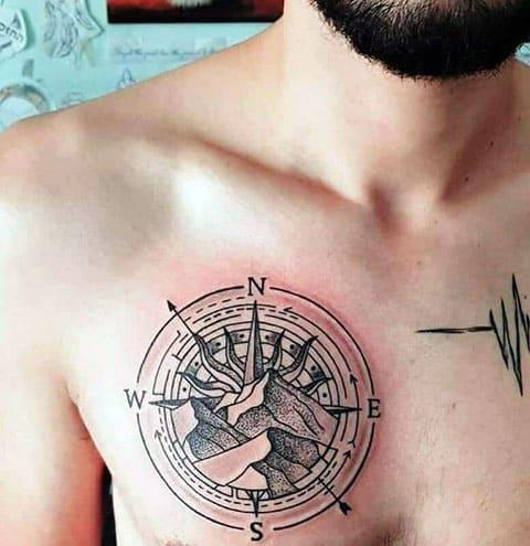 Татуировка на грудине с компасом и скалами