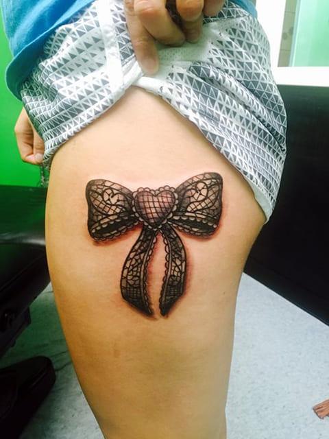 Татуировка с подвязкой на женском бедре