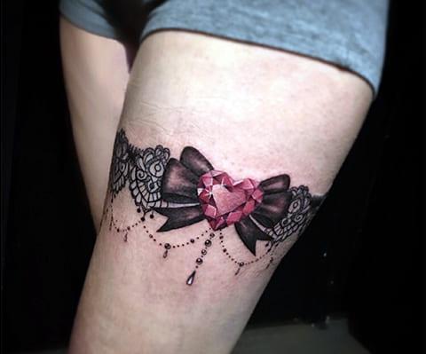 Татуировка подвязка на бедре у девушки