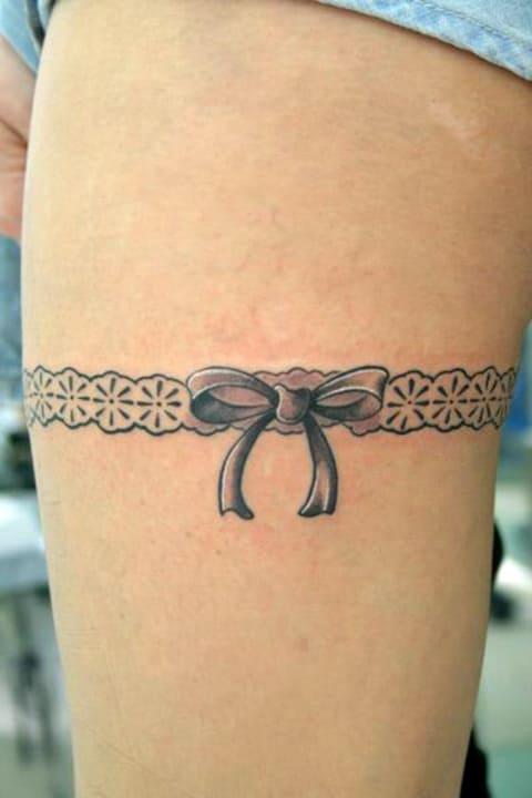 Татуировка с подвязкой на бедре у девушки - фото