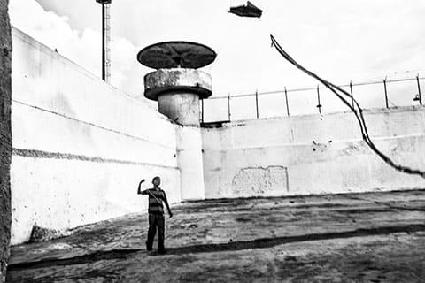 Ребенок запускает воздушного змея перед постом охраны Боливарианской Национальной гвардии. Национальная гвардия несет ответственность за обеспечение безопасности в венесуэльских тюрьмах