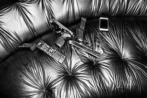 9-миллиметровый пистолет и iPhone 5, принадлежащее одному из заключенных, лежат на диване в гостиной одного из тюремных лидеров