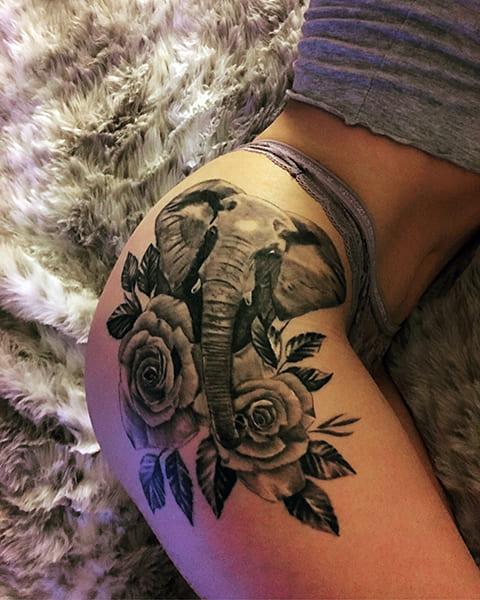 Татуировка слон и цветы у девушки на бедре