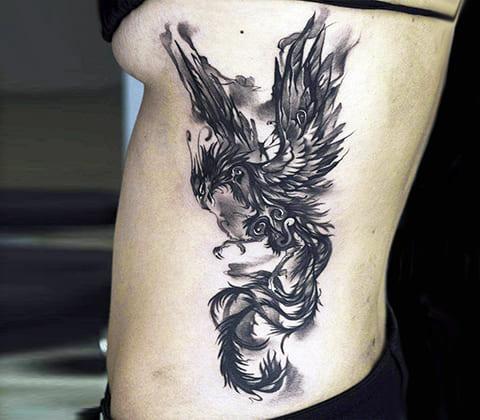Татуировка с фениксом на боку у девушки