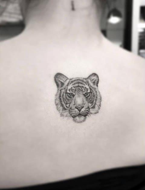 Тату голова тигра на спине у девушки - фото
