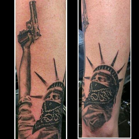 Тату Статуя Свободы с маской и пистолетом