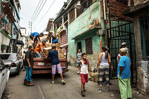 Жители Петаре (большой трущобы на окраине Каракаса) доставляют продовольственные ящики с продуктами, выданные правительством