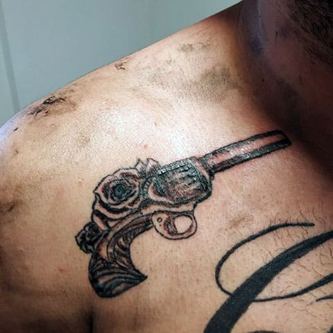 Тату револьвер на плече