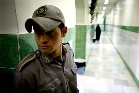 Тюремный охранник стоит вдоль коридора в тюрьме Эвин в Тегеране