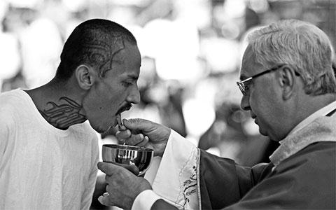 Член банды Mara Salvatrucha получает причастие от священника