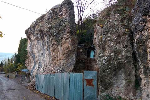 Сверху на скале, которую дробят, расположены частные дома