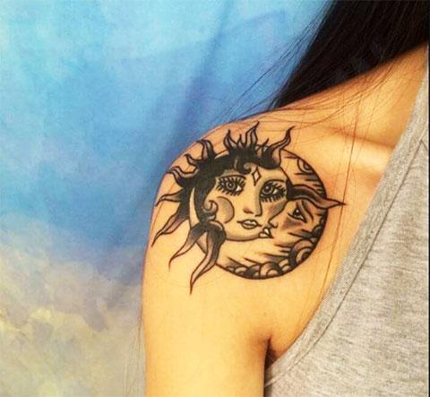 Татуировка солнца с луной в стиле инь-янь у девушки а плече