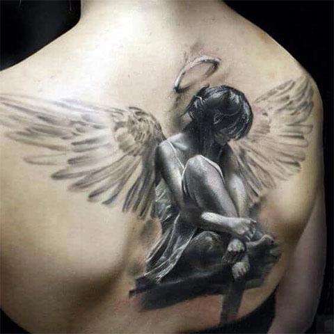 Объемная татуировка ангела на спине девушки