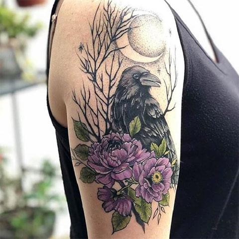 цветное тату ворон у девушки на руке
