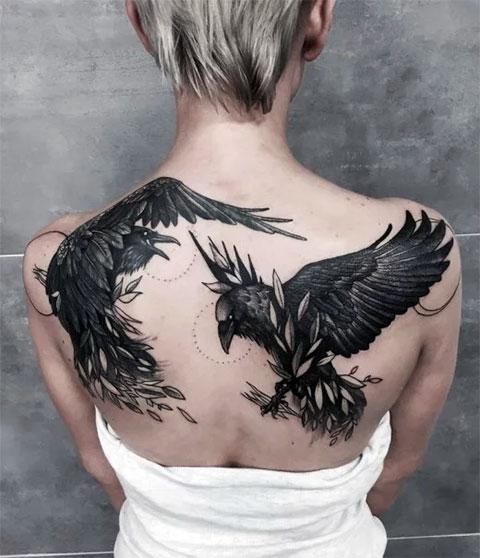 Тату с двумя воронами на спине у девушки - фото