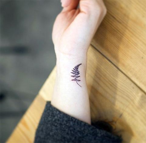 Маленькая татуировка папоротника на руке женщины