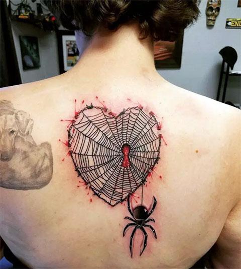 Паук с паутиной на спине у девушки - татуировка